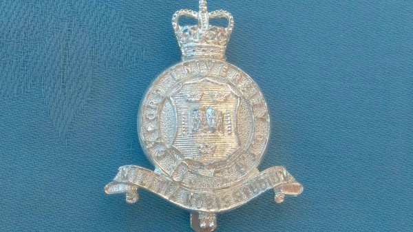 The Oxford University Officers Training Corp cap badge.