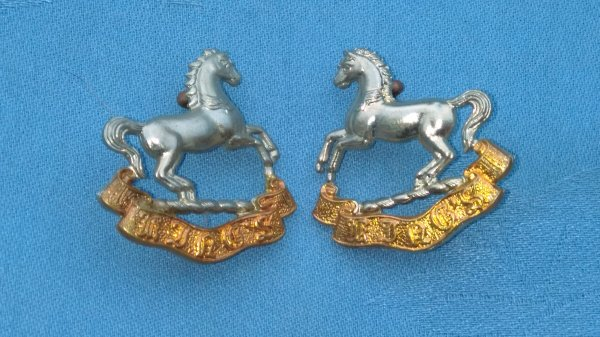 The Kings Regiment collar badges.