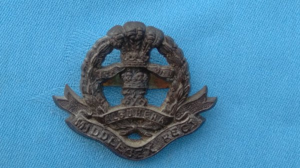 The Middlesex Regiment cap badge.