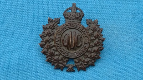 The Queens University Contingent Canadian Officer Training Corp cap badge.
